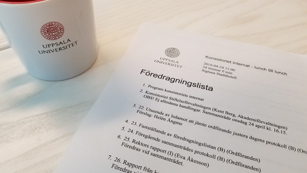 A coffee cup and the printed agenda of the University Board meeting.